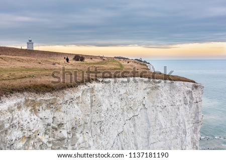 Panoramic photo of White Cliffs of Dover  during Early Spring 2017. Limestone chalk cliffs. Footpath on the edge during sunset. Kent County, Dover.
