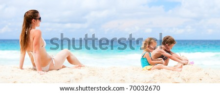 Panoramic photo of young mother and her two kids at beach