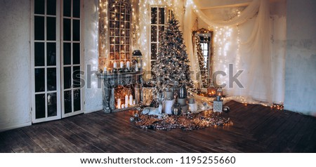 panoramic photo warm, cozy evening in Christmas room interior design,Xmas tree decorated by lights presents gifts toys, candles, lanterns, garland lighting indoors fireplace.holiday living room.New  #1195255660