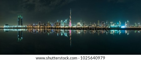 Panoramic picture for dubai city reflected on the water.
