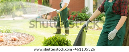 Panoramic picture of two gardeners working in a garden and watering the lawn