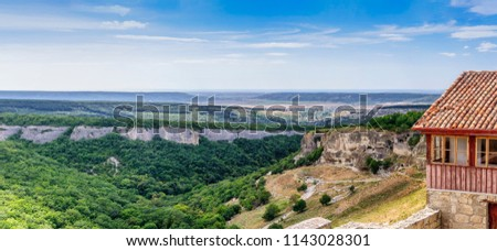 Panoramic picture. The valley of Josaphat. On the right is the rocky medieval cave town of Chufut-Kale. Next, the Assumption Rock. In the distance the city of Bakhchisaray. Republic of Crimea.