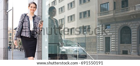 Panoramic portrait of beautiful business woman in financial district, glass reflections space, holding smart phone, looking outdoors. Professional elegant female using technology, office buildings.