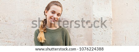 Panoramic portrait of beautiful teenager girl leaning on textured stone wall outdoors, looking smiling. Young friendly woman tourist student recreation lifestyle, simple beauty portrait wall space.
