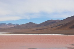 Panoramic portrait red water lake at Laguna Colorada (Red Lagoon) in latin Eduardo Avaroa Andean Fauna National Reserve in colorful wild Altiplano at beautiful Andes mountains, Bolivia, South America.