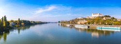Panoramic scenery view of Danube river in Bratislava, Slovakia. Bratislava Castle building on the right. Sunny autumn day