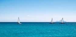 Panoramic sea view with three sailing boats cruising on the ocean.
