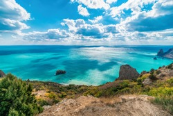 Panoramic seascape, calm azure sea, clouds and bright sky. View of the Black Sea coast in Crimea, Cape Fiolent in Sevastopol. Copy space. The concept of calmness, silence and unity with nature