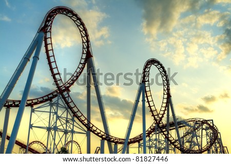 Panoramic shot of a roller coaster's loop at sunset.