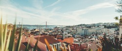 Panoramic shot of a sunny Lisbon cityscape from the high above; the panorama of Lisbon urban landscape with plenty of antique and modern houses and a suspension bridge over Tagus river in a background