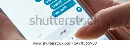 panoramic shot of abuser sending offensive messages while using smartphone, illustrative editorial #1478565989