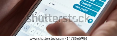 panoramic shot of abuser typing offensive messages while using smartphone, illustrative editorial #1478565986