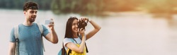 panoramic shot of asian woman taking photo and handsome man using smartphone