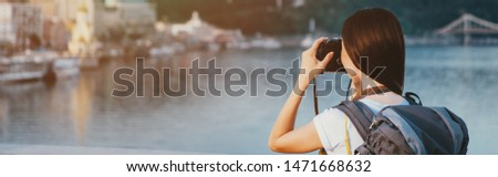 panoramic shot of brunette woman with backpack taking photo
