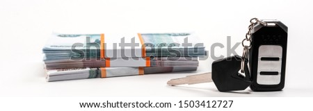 panoramic shot of car key with key chain near stacks of russian money on white  #1503412727
