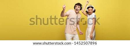 panoramic shot of excited man and woman dancing while listening music in headphones on yellow background #1452507896