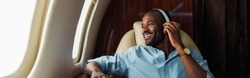panoramic shot of happy african american man listening music in private plane