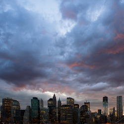 Panoramic shot of Manhattan skyline from the Brooklyn bridge at dusk.