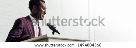 panoramic shot of panoramic shot of african american businessman in formal wear talking during conference  #1494804368
