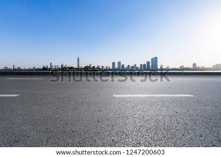 Panoramic skyline and buildings with empty concrete square floor #1247200603