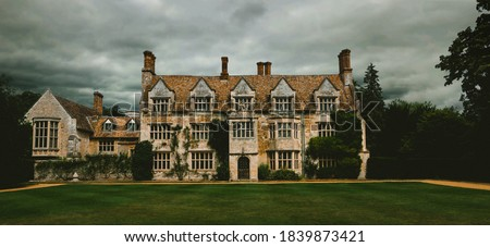 Panoramic, spooky old english manor house with lawn trees. Dramatic cloudy and overcast sky