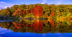 Panoramic stunning photo of fall foliage reflected on a lake with a glass like mirror water surface