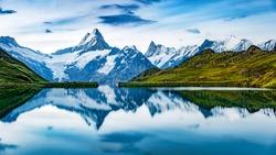 Panoramic summer view of Bachalpsee lake with Schreckhorn and Wetterhorn peaks on background. Gloomy outdoor scene of Swiss Bernese Alps, Switzerland, Europe.
