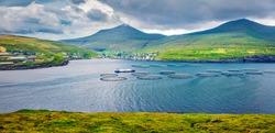 Panoramic summer view of Sandavagur village, Faroe Islands, Kingdom of Denmark, Europe. Gloomy morning view of fish farm on Vagar island. Traveling concept background.