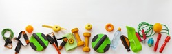Panoramic top view of a set of sports equipment for fitness at home. Wellness and health promotion concept. Orange and green workout tools and fruits on white background. Flat lay, copy space, banner