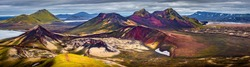 Panoramic unreal magic Icelandic landscape of colorful rainbow volcanic Landmannalaugar mountains, red and pink volcanic crater Stutur at famous Laugavegur hiking trail with dramatic sky, Iceland