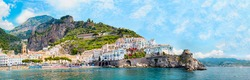 Panoramic view, aerial skyline of small haven of Amalfi village with tiny beach and colorful houses located on rock. Tops of mountains on Amalfi coast, Salerno, Campania, Italy.