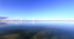 Panoramic view at clean blue water and sky. Natural summer background. Blue sky over calm lake.