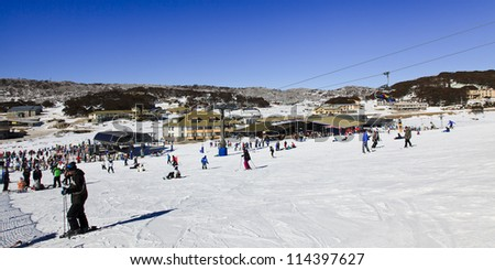 panoramic view at ski resort village from snowy hill on sunny winter day cold and snow sport people having fun skiing and snowboarding