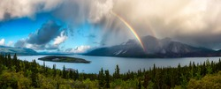 Panoramic View Canadian Nature, Mountains, and Lake during fall season. Sunny Cloudy morning with Rainbow. Located in Carcross, near Whitehorse, Yukon, Canada. Background Panorama
