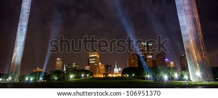 Panoramic view City of St. Louis skyline at night as seen between the arch legs lit up with flood lights
