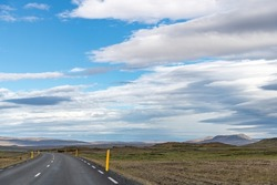 Panoramic view down a curving two lane road on Iceland, through barren Icelandic Highlands with volcanos and mountains in northern part of the country with beautiful blue sky with white fluffy clouds