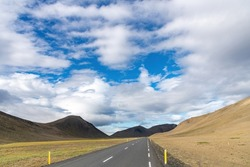 Panoramic view down a two lane road on Iceland, through barren Icelandic Highlands with volcanos and mountains in the northern part of the country with a beautiful blue sky with white fluffy clouds