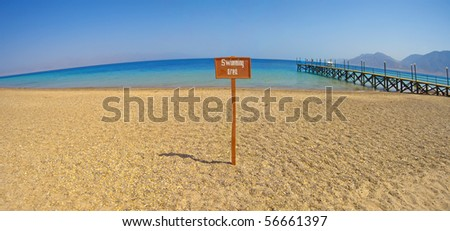 Panoramic view from a tropical beach with swimming area sign - stock photo