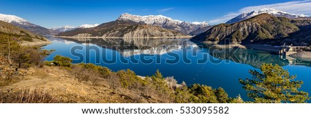 Panoramic view from hiking trail of Serre Poncon Lake in Winter with snow covered mountains. Le Rousset, Hautes Alpes, Southern French Alps, France