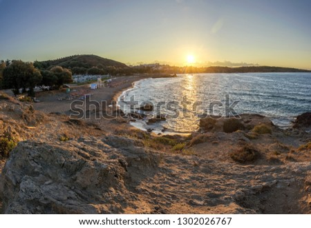 Panoramic view from hill on a rocky coast with a bay at a sunset - Chrissi Akti beach near Chania (Crete, Greece)