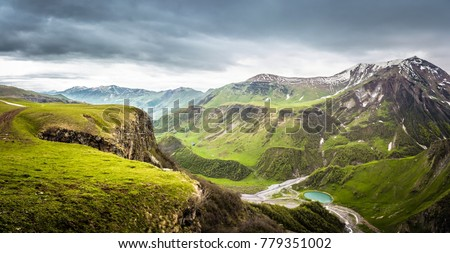 Panoramic view from the grassy hill on the Kazbek mountains and the green valley crossed with roads and with a blue lake in Georgia against cloudy sky #779351002