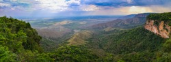Panoramic view from top of cliffs in an opening valley in the late afternoon with clouds and sunrays, Chapada dos Guimarães, Mato Grosso, Brazil, South America