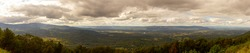Panoramic view if Shenandoah valley observed from a scenic overlook by skyline drive. image features vast forests covering hills and mountains of blue ridge mountain range.