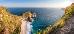 Panoramic view Karang Dawa, Manta Bay or Kelingking Beach on Nusa Penida Island, Bali, Indonesia. Tropical beach with a turquoise ocean among the rocky cliffs. Sunset on a tropical island. Travel