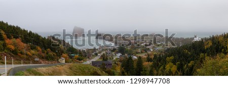 Panoramic view of a beautiful modern town on the Atlantic Ocean Coast during a hazy day. Taken in Perce, Quebec, Canada.