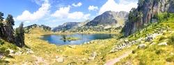 Panoramic view of a beautiful natural lake in the mountains. Llac del Circ de Colomers, Pirineus, Salardú, Naut Aran, Val d'Aran, Lleida, Catalonia, Spain.