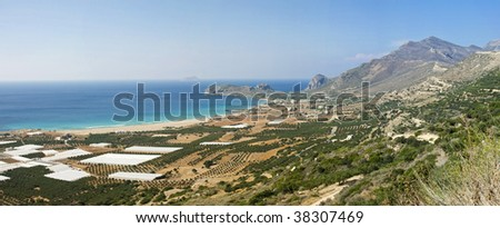 Panoramic view of a Cretan coast. Photo taken in a North-West part of the island. The place is called Falasarna Beach. White shapes are the greenhouses.