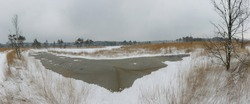 Panoramic view of a frozen lake during cold winter in the moorlands of Belgium