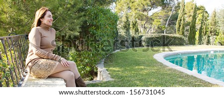 Panoramic view of a home owner relaxing in her country home garden with trees and a swimming pool during a sunny autumn morning, sitting on a stone wall with veranda balcony.