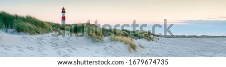 Photo of  Panoramic view of a lighthouse standing at the coast of Sylt, North Sea, Germany
